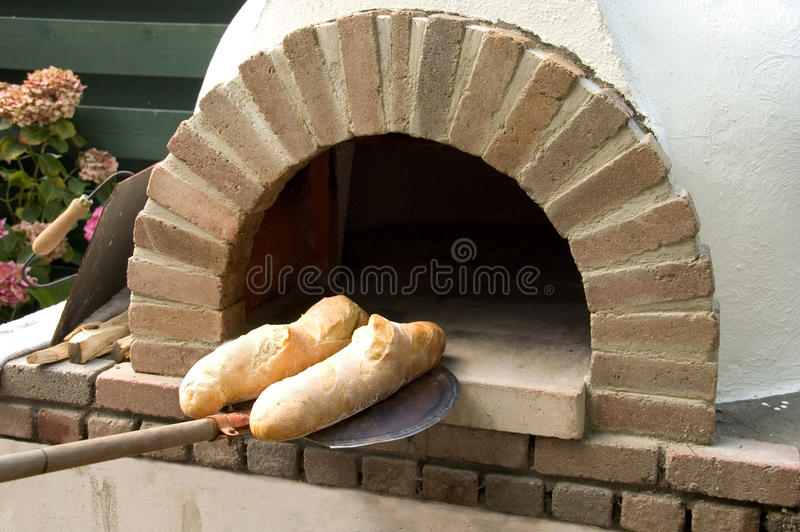 Bread with Oven. Two freshly baked loafs of bread in front of a traditional wood oven outside