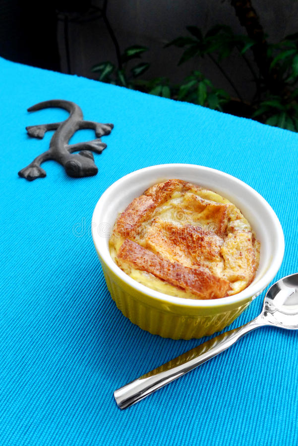 Bread pudding baked, home cooked dessert. A photograph showing a simple homecooked desert dish of baked whole meal bread, egg and milk pudding in a yellow royalty free stock photo