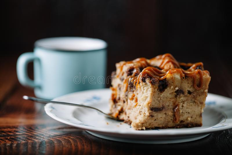 Bread pudding with caramel sauce served with a cup of hot cocoa. On dark rustic background royalty free stock image