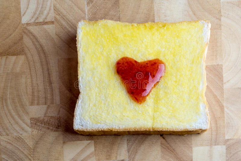 Bread and red heart shaped jam on wooden royalty free stock photos