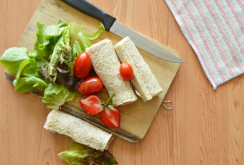 Bread roll and salad on chop block royalty free stock photo