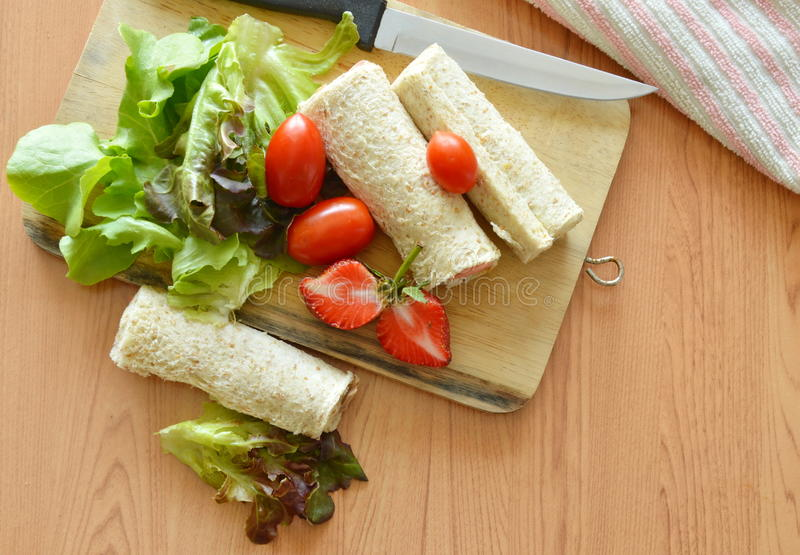 bread roll and salad on chopping block stock photo