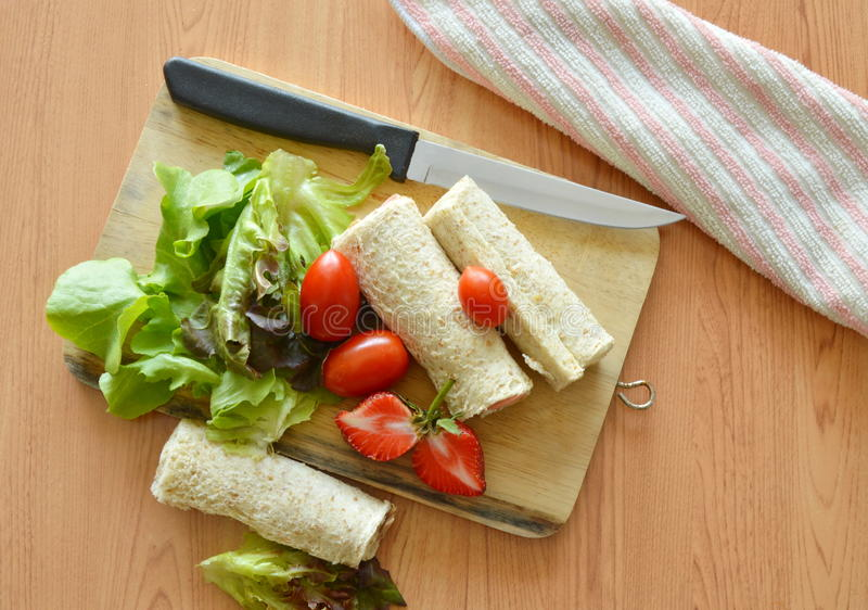 Bread roll and salad on cutting board stock images