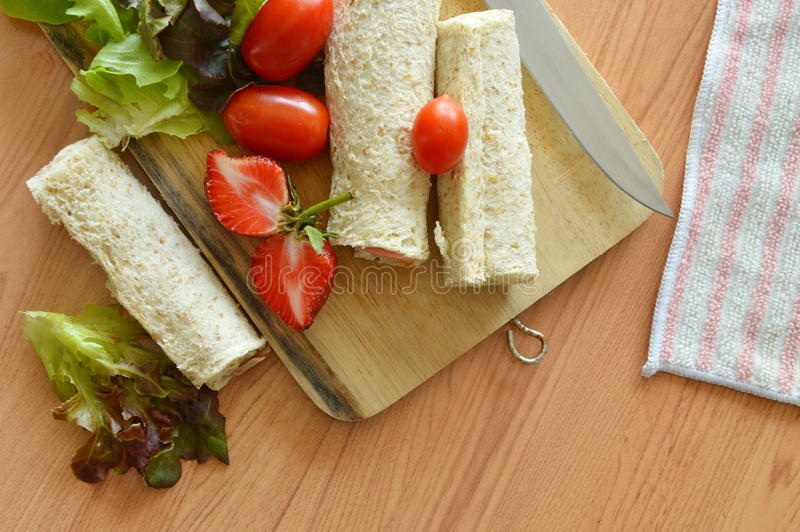 Bread roll and salad on cutting board royalty free stock image