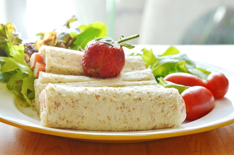 Bread roll and salad topping strawberry on dish stock photography