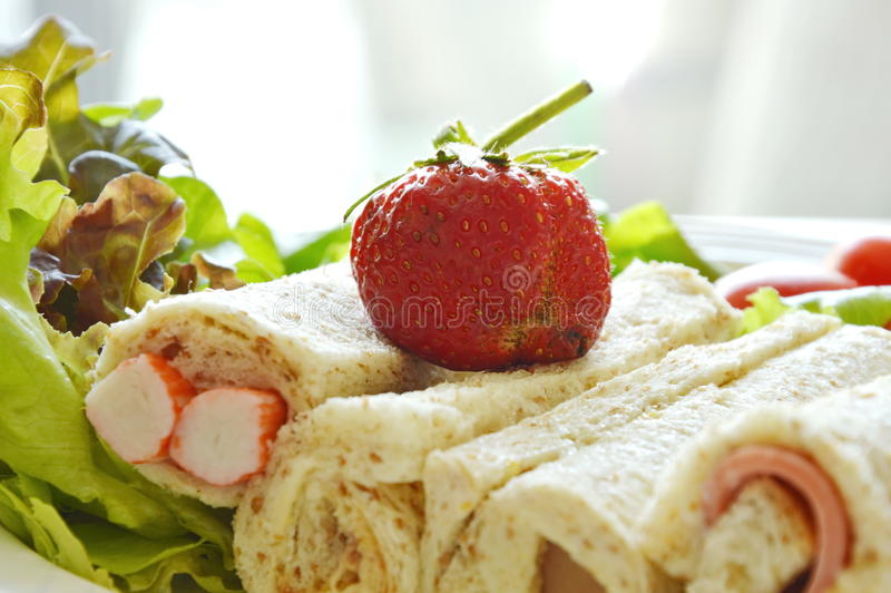 Bread roll and salad topping strawberry on plate royalty free stock photo