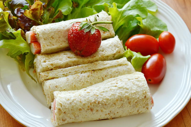 Bread roll and salad topping strawberry on plate stock image