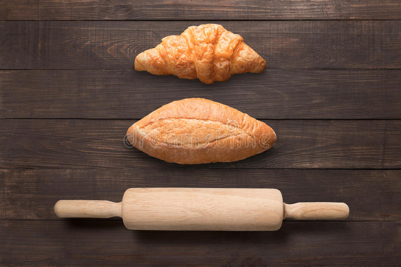 Bread and rolling pin on wooden background from top view stock photo
