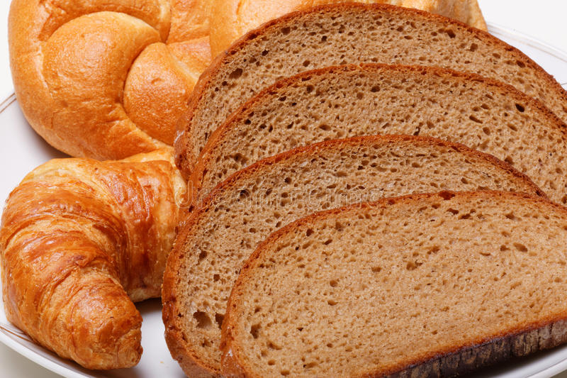 Bread rolls and brioche. Sliced brown bread with rolls and brioche on plate stock photography
