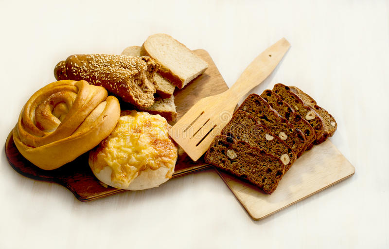 Bread, rolls and pastries on the cutting board stock images