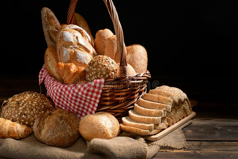 Bread and rolls in wicker basket on burlap sack stock images