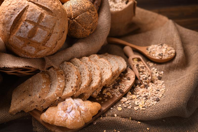 Bread and rolls in wicker basket on burlap sack royalty free stock images