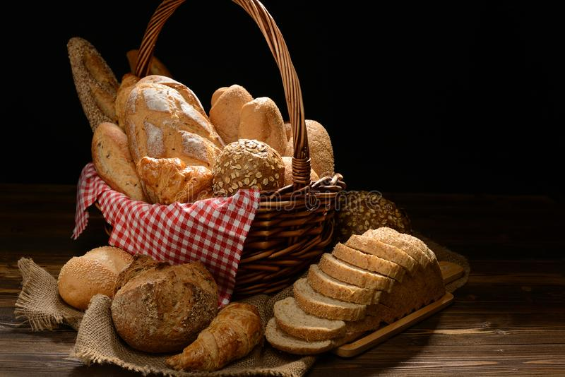 Bread and rolls in wicker basket on burlap sack royalty free stock image