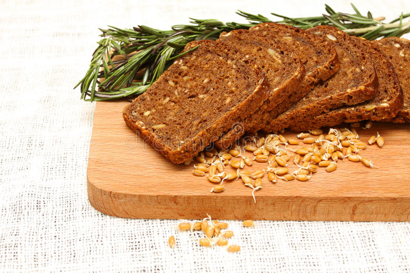 Bread, rosemary and wheat germ on a wooden board. On the white linen tablecloths royalty free stock image