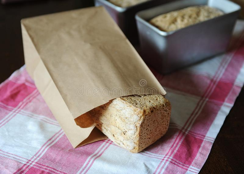 Bread on a rye ferment without yeast in a paper bag on a checkered tablecloth. Loaves in baking forms in the background stock photography