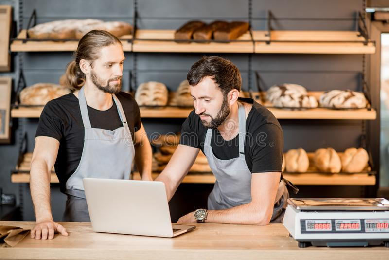 Bread sellers working in the bakery shop. Two handsome sellers in uniform working with laptop standing at the counter of the bakery shop stock photography
