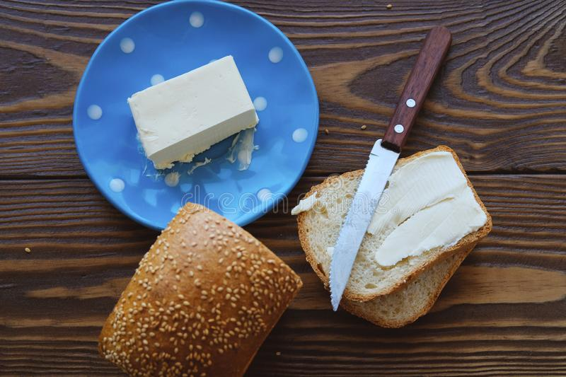 Bread with sesame and butter on a rustic wooden table. Making toast and sandwiches for Breakfast or lunch. The concept of organic. Healthy food. Copy space stock photo