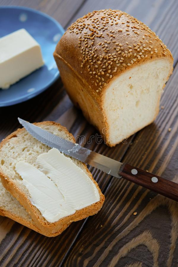 Bread with sesame and butter on a rustic wooden table. Making toast and sandwiches for Breakfast or lunch. The concept of organic. Healthy food. Copy space stock photography