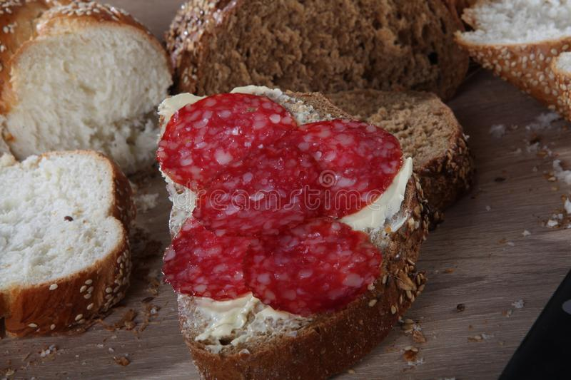 Bread with sesame, butter and sausage close-up royalty free stock photo