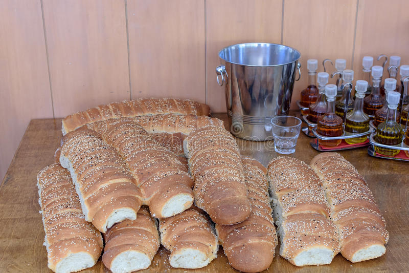 Bread with sesame lies on a wooden table and next is olive oil in bottles stock image