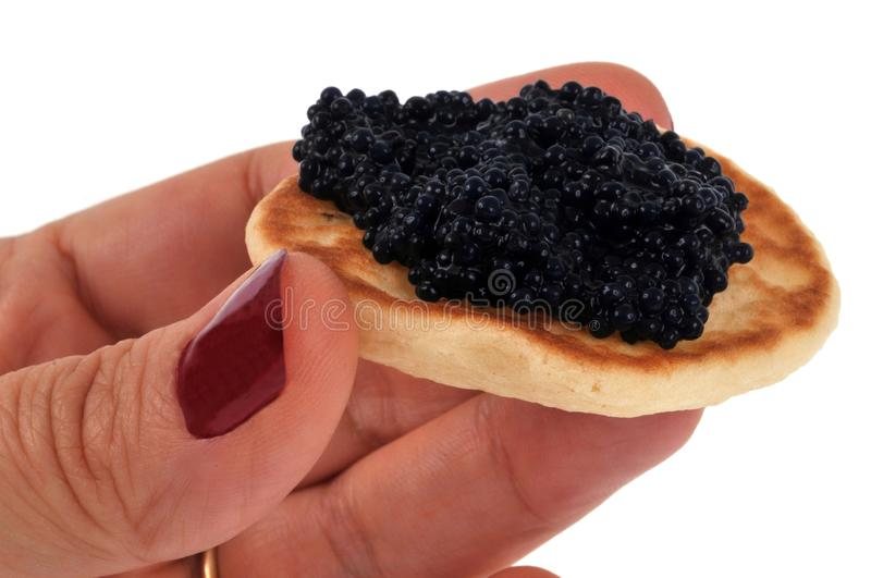 Toast of caviar in hand on white background. Bread slice with black lump eggs in close-up stock photos