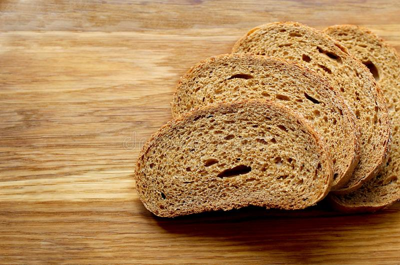 Black bread sliced on slices lying on a cutting board. Bread, sliced, top, view, background, wooden, brown, food, slice, healthy, organic, table, fresh, rye stock photos