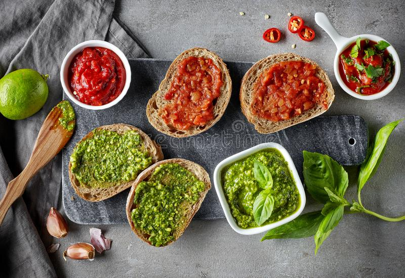 Bread slices with basil pesto and garlic tomato sauce royalty free stock image