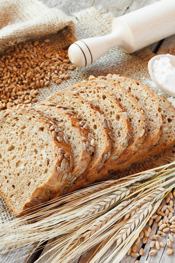 Bread slices, rolling pin, grain and rye ears on table royalty free stock photos