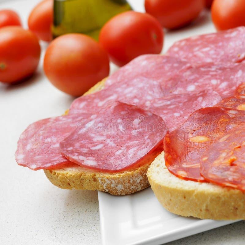 Bread slices with spanish salchichon and chorizo stock photography