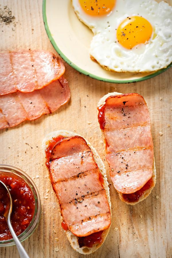Bread slices with tomato relish, turkey rasher and fried egg.  royalty free stock photography