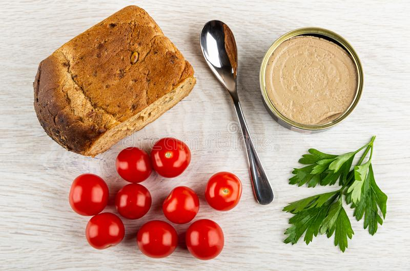 Bread, spoon, jar with liver pate, tomato cherry, leaves of parsley on wooden table. Top view royalty free stock photos
