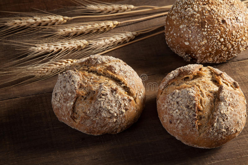 Bread and wheat ears on wooden background royalty free stock photography