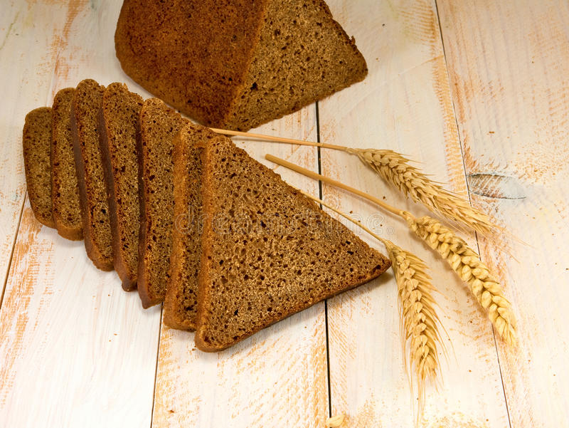 Bread and wheat on the table. Bread and wheat on the wooden table royalty free stock image