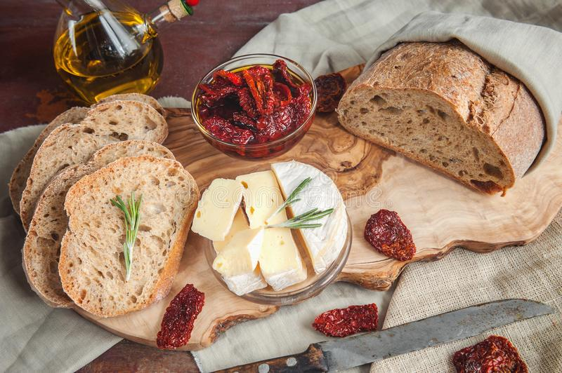 Bread whole wheat processed cheese Camembert with sun-dried tomatoes with rosemary and olive oil. royalty free stock images