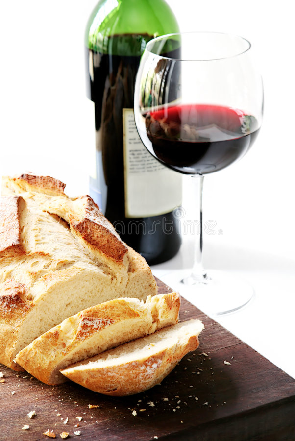 Bread and Wine. Red wine with fresh sliced sourdough bread - the staples of life! High-key effect stock image
