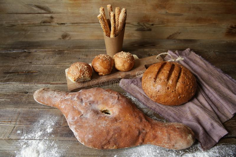 Bread on a wooden rustic table, bread buns on a wooden board and bread sticks with sesame seeds with copy space for text stock photography