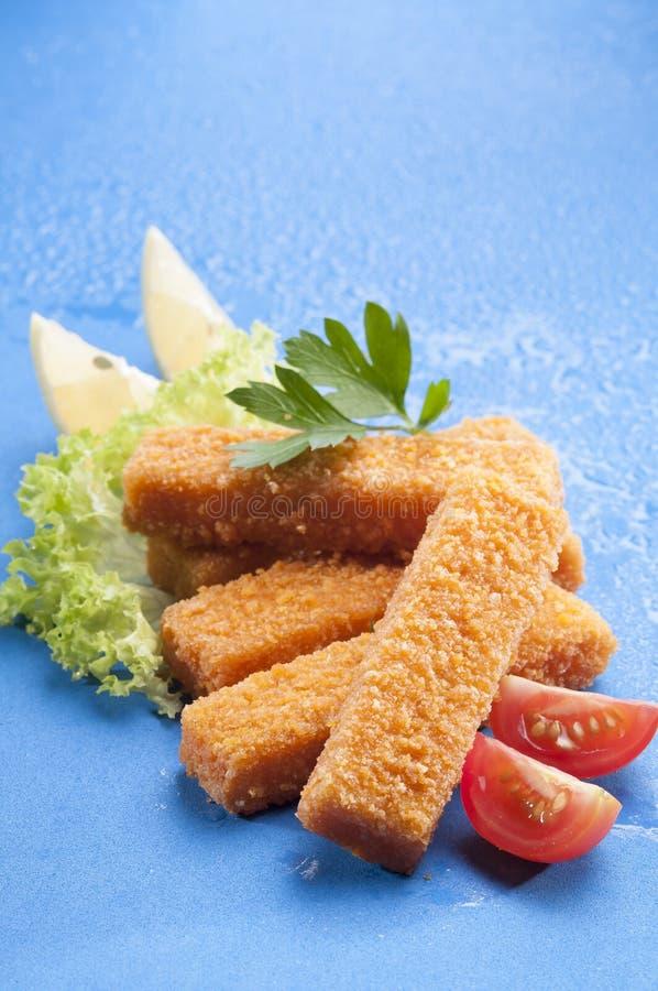 Breaded briet Fischstäbchen mit Kopfsalat- und Kirschrottomate mit Zitronenscheibe auf blauem Hintergrund mit Wasserspritzen lizenzfreie stockbilder