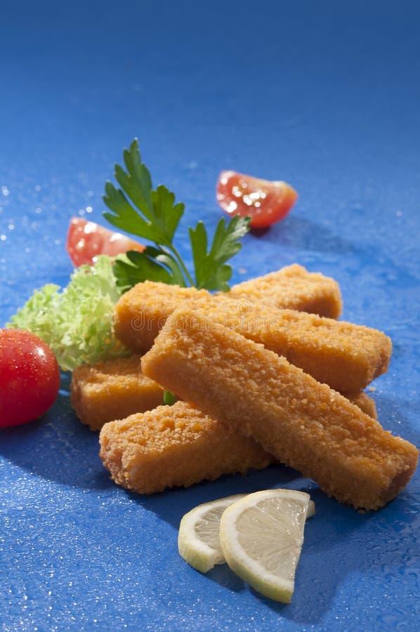 Breaded briet Fischstäbchen mit Kopfsalat- und Kirschrottomate mit Zitronenscheibe auf blauem Hintergrund mit Wasserspritzen stockfotografie