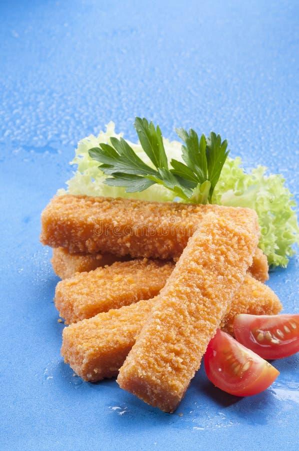 Breaded briet Fischstäbchen mit Kopfsalat- und Kirschrottomate mit Zitronenscheibe auf blauem Hintergrund mit Wasserspritzen stockbild