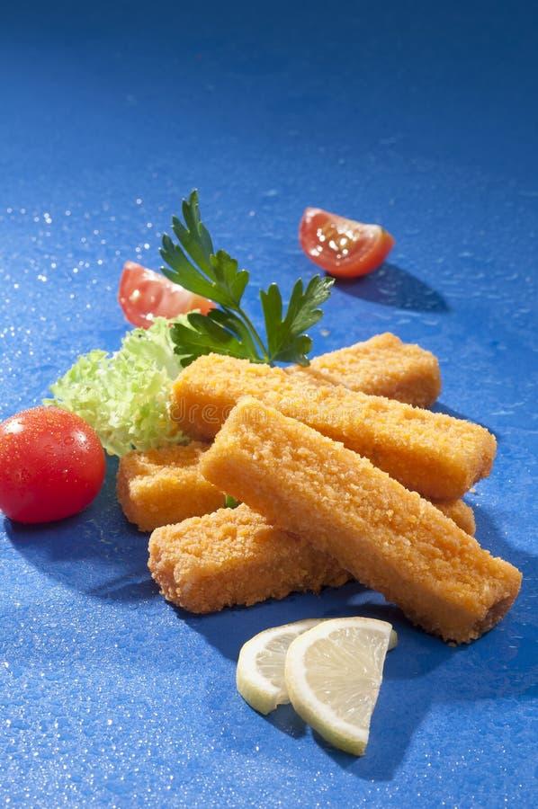 Breaded briet Fischstäbchen mit Kopfsalat- und Kirschrottomate mit Zitronenscheibe auf blauem Hintergrund mit Wasserspritzen lizenzfreie stockfotos