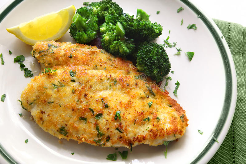 Breaded Chicken. Breaded and herbed chicken breast fillet, served with broccoli and lemon. Delicious chicken schnitzel stock images