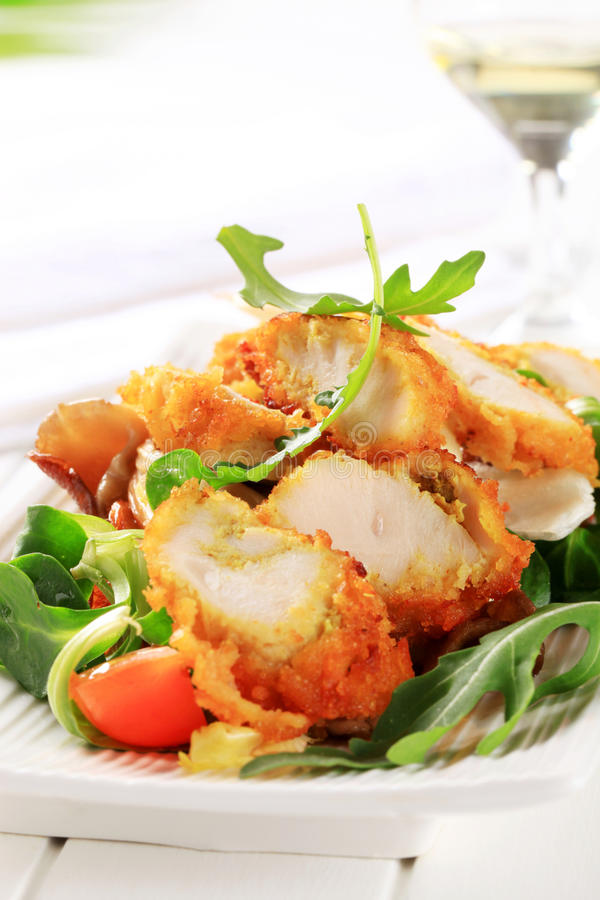 Breaded chicken breast with salad greens stock images