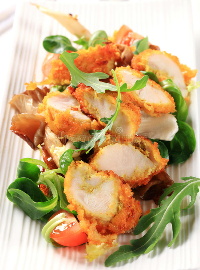 Breaded chicken breast with salad greens royalty free stock image