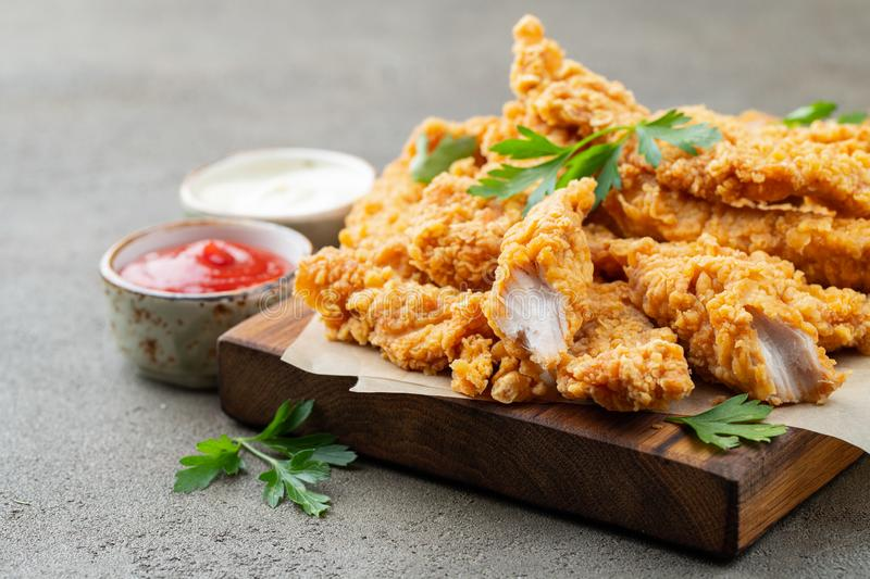 Breaded chicken strips with two kinds of sauces on a wooden Board. Fast food on dark brown background.  royalty free stock photography