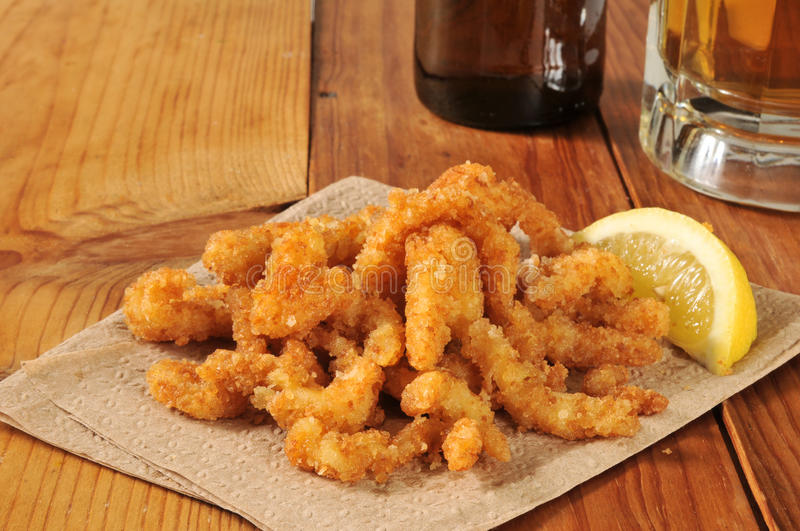 Breaded strips. Breaded, deep fried strips with a wedge of lemon and beer stock photos