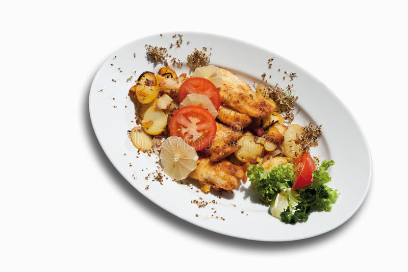 Breaded coalfish fillet with fried potatoes in plate on white ba. Breaded coalfish fillet with fried potatoes in plate isolated on white background royalty free stock image