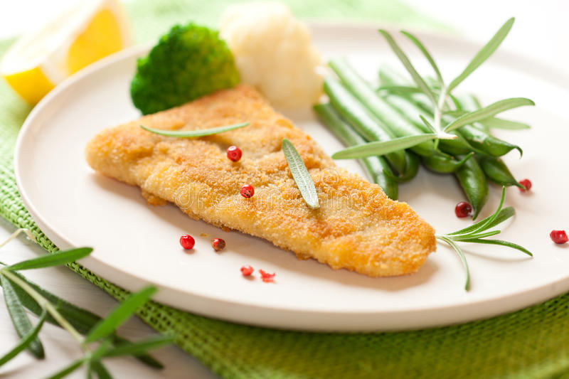 Breaded fish fillet with vegetables royalty free stock image