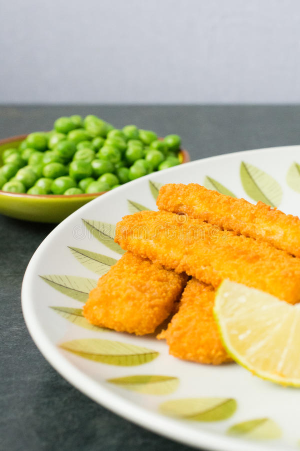 Breaded fish fingers with peas royalty free stock photography