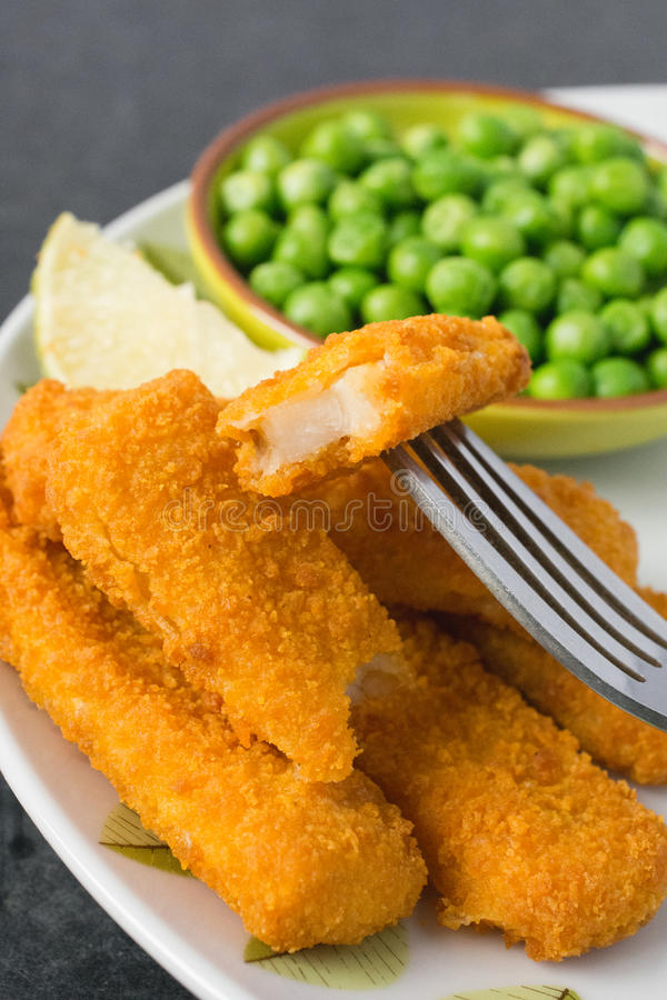 Breaded fish fingers with peas. Breaded and Baked Fish Sticks, fingers on a plate with a bowl of peas and a slice of lemon stock photo