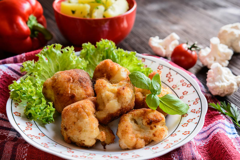 Breaded fried cauliflower with potatoes. Breaded fried cauliflower with boiled potatoes on a wooden background stock photo